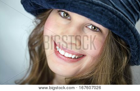 Pretty girl with old blue velvet hat in the grunge style is smiling at camera
