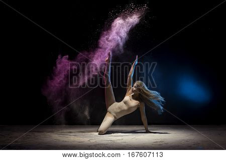 Young long haired blonde in beige bodysuit posing in cloud of pink and blue dust raising her leg gracefully up studio shot