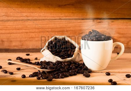 The Coffee Beans And Cup Of Coffee With Smoke On Wooden Table Background. Still Life Process