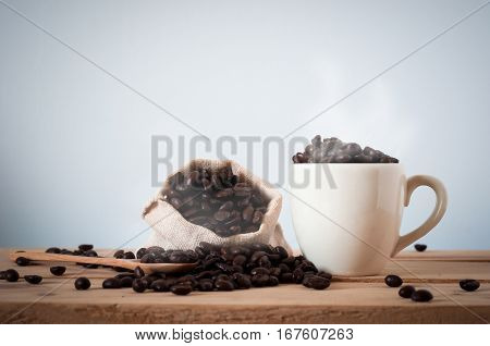 The Coffee Beans And Cup Of Coffee On Wooden Table Background. Still Light Process