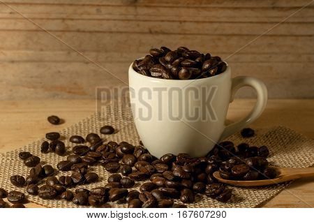 The Coffee Beans And Cup Of Coffee On Sack With Spoon Onwooden Table Background. Still Life Process