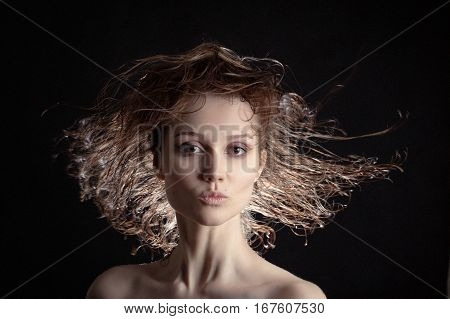 beautiful woman with flying wet hair on black background