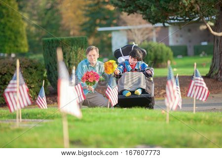 Father and disabled son in wheelchair holding flowers and visiting grave site in cemetery covered with American flags