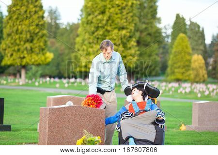 Father and disabled son in wheelchair holding flowers and visiting grave site in cemetery