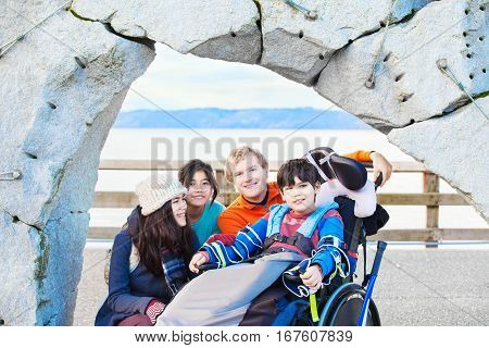 Smiling disabled ten year old boy in wheelchair surrounded by friends and family outdoors near ocean water in background.