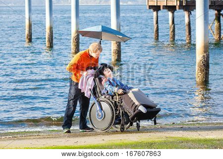 Smiling disabled ten year old boy in wheelchair being cared for by friend or family outdoors near ocean water in background.