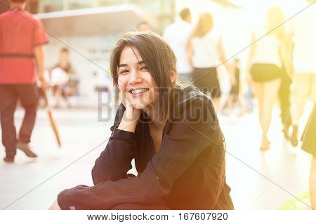Beautiful biracial teen girl sitting by sidewalk head in hand smiling at camera with morning sunshine from the side