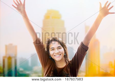 Biracial teen girl standing with arms raised up smiling with morning sunshine hitting skyscapers and buildings in background