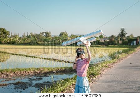 Cute Asian Girl Playing Toy Plane As Pilot Imagination To The Future At Flower Grass Field Vintage F