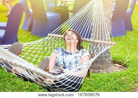 Beautiful biracial teen girl relaxing in hammock outdoors on sunny morning