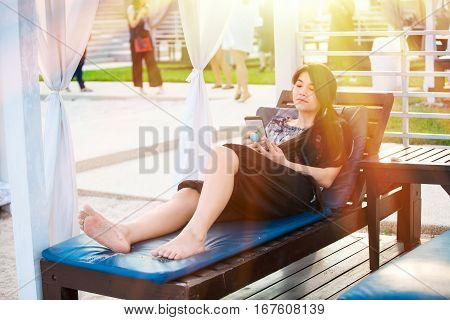 Beautiful biracial teen girl sitting under sun shade with white curtains at resort using smartphone