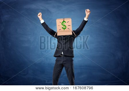 Businessman wearing cardboard box with drawn dollar sign on his head on the blue blackboard background. Make profits. Business development. Rise in profitability.