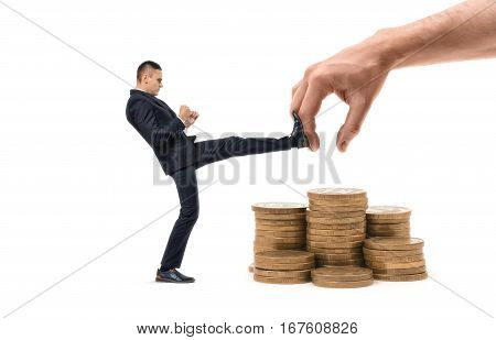 Businessman is hitting with a leg a huge hand trying to grab his profit on the white background. Profit protecting. Small business protection. Market competition