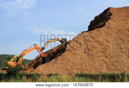 Mountain of Wood chips with Backhoes working around