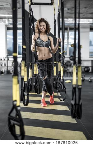 Smiling sportive woman with curly hair stands in the gym on the background of the partition. She wears dark sportswear with red sneakers. She looks into the camera and holds TRX straps. Vertical.
