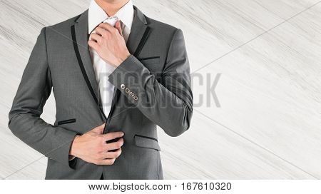 business man hand holding necktie in grey suite on wooden background. smart guy