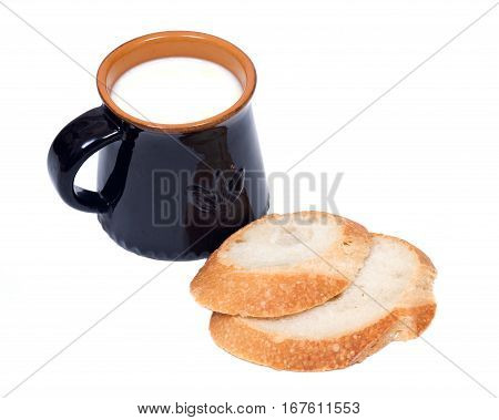 Cream top organic whole milk in ceramic cup and sliced crusty country style round organic french bread isolated on white background