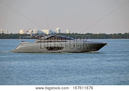 Sleek silver motor yacht at idle in the florida intra-coastal waterway near Miami Beach.