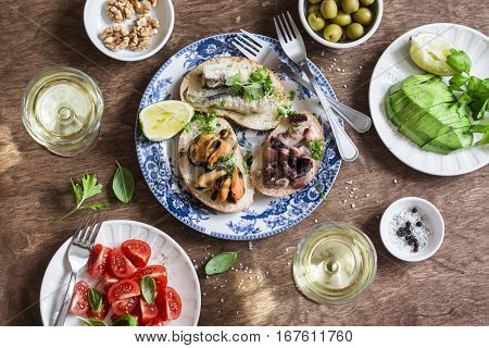 Delicious tapas - sandwiches sardines mussels octopus grape olives tomatoavocado and white wine on wooden table top view. Flat lay