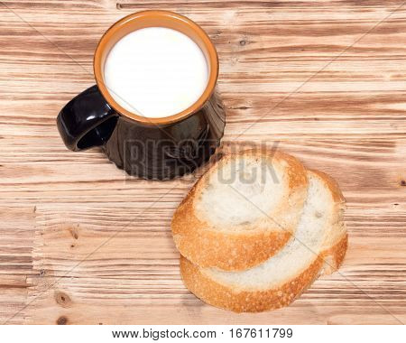 Cream top organic whole milk in ceramic cup and sliced crusty country style round organic french bread on wooden vintage tray