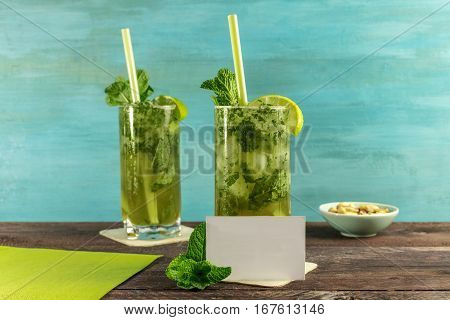A photo of mojito cocktails with mint leaves, wedges of lime, and a snack, on a vibrant teal wooden background with a business card for copy space. Selective focus