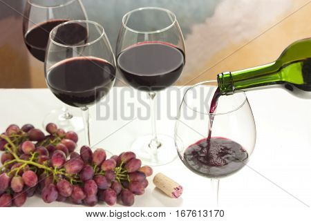 Photo of red wine poured into glass from bottle, with more blurred full wine glasses in the background, and also out of focus grapes and cork