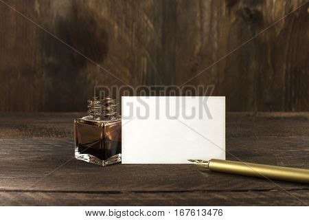 A photo of a blank white thick cardboard business card on a dark wooden background texture with a golden ink pen and ink bottle. A mockup or a minimalist banner with copy space