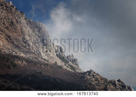Slope mountain with scattered stones on a background of blue sky with clouds