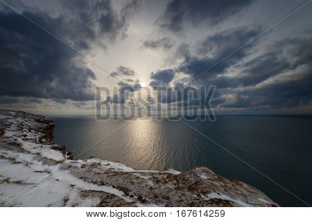 Seacoast in the snow under heaven with clouds