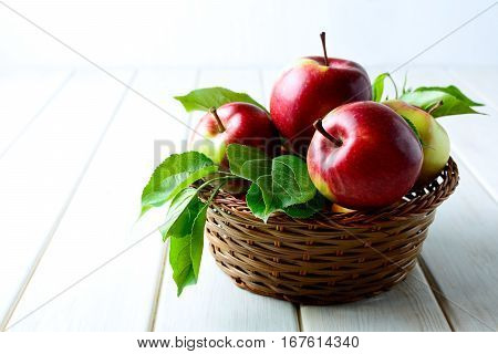 Fresh red apples in the wicker basket. Ripe fruits as abundant harvest concept. Copy space.