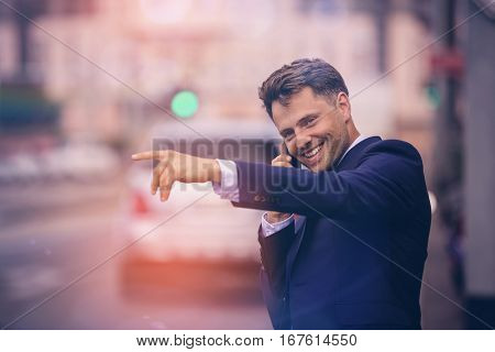 Handsome businessman hailing taxi while taking on phone at street
