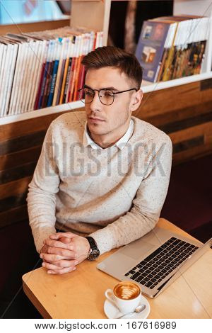 Image of concentrated young man wearing eyeglasses sitting in cafe and looking aside.