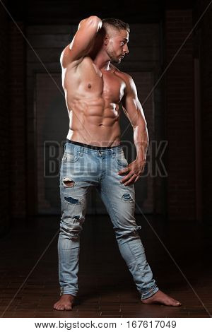 Young Bodybuilder In Jeans Flexing Muscles
