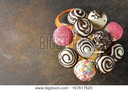 Various cake pops decorated with white and dark chocolate on a brown background
