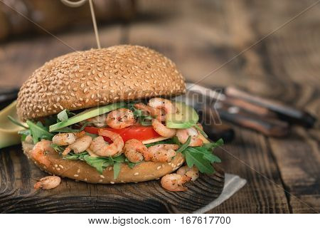 Burger with grilled shrimp arugula and avocado on a wooden board close up with copy space