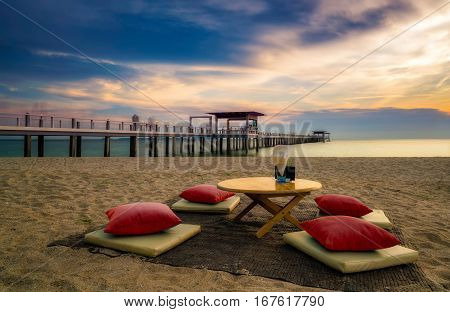 Exotic twilight dining seat on the beach. Selective focus on the dining beach table