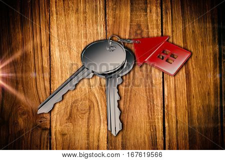 Metallic key with red home ring against wooden table