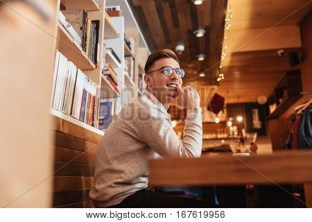 Picture of young smiling man wearing glasses dressed in shirt sitting in cafe while looking aside.