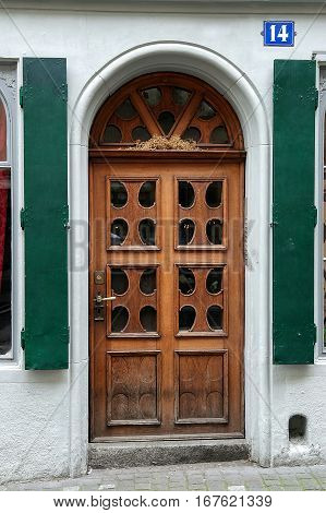 old wooden arched door with green shutters