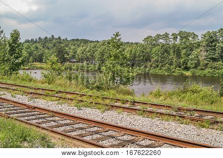 Rusty railroad tracks running parallel to the Hudson River in New York