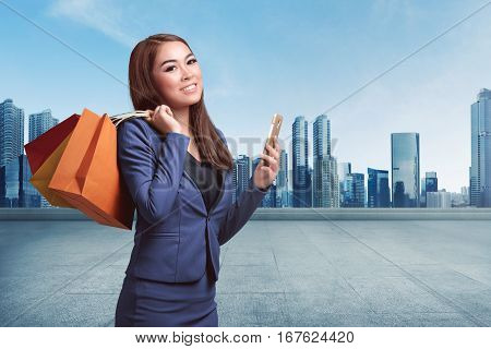 Beautiful Asian Business Woman With Shopping Bags Using Her Smartphone