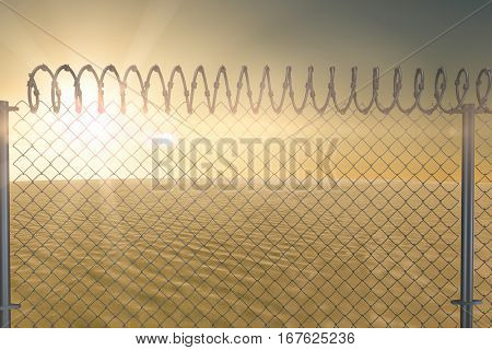 Chainlink fence against white background against desert scene