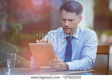 Confused businessman using digital tablet at sidewalk cafe