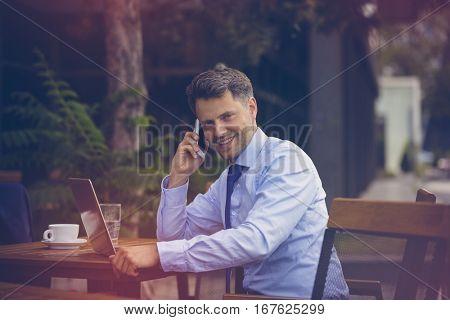 Portrait of handsome businessman talking on mobile phone while using laptop at sidewalk cafe