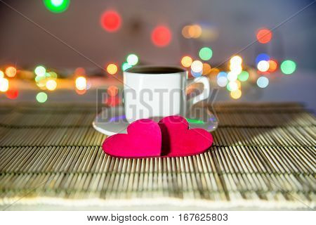 cup of coffee and two red hearts on the background illumination