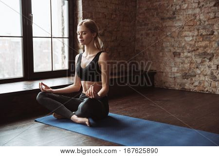 Relaxed young sportswoman doing yoga and meditating in studio