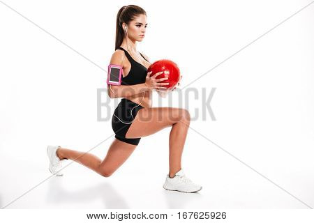 Side view portrait of a young pretty sportswoman doing squats with heavy fitness ball and listening to music isolated on a white background
