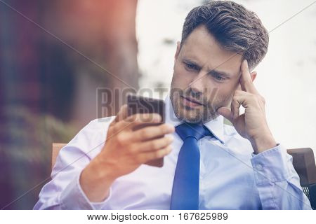 Close up of tensed businessman using mobile phone