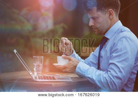 Handsome businessman having tea while using laptop at sidewalk cafe