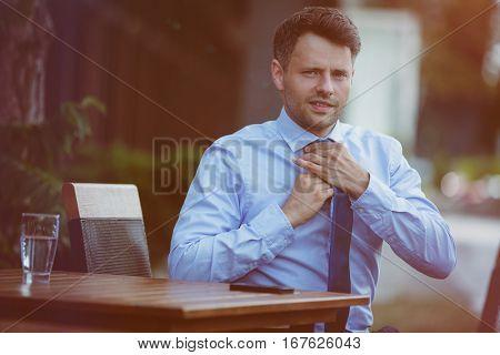 Portrait of businessman adjusting his tie at sidewalk cafe